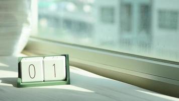 mano cambiando el bloque de calendario de madera blanca de 1 a 2