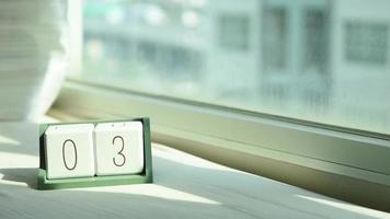mano que cambia el bloque de calendario de madera blanca de 3 a 4
