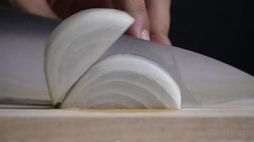 o chef usa uma faca de cozinha para cortar cebolas