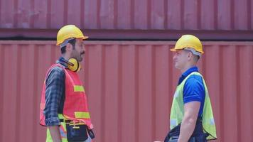 Two cargo container workers shake hands  video