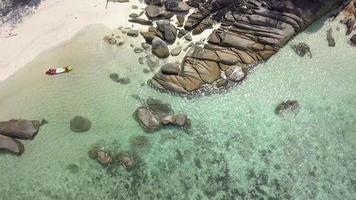 Kajak im blauen Meer nahe Rock Shore Overhead-Antenne video