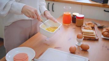 mãos de mulher batem ovos em uma tigela
