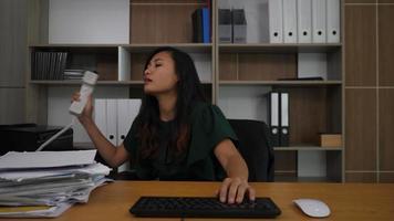 trabalhadora de escritório bonita digitando em um laptop no trabalho