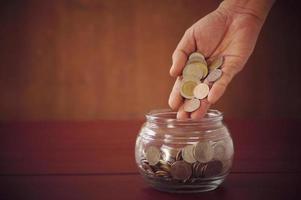mano poniendo monedas en un frasco de vidrio foto