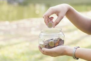 Hand putting coins into a glass jar photo