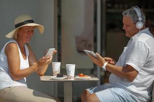 Mature couple eating outside with electronics