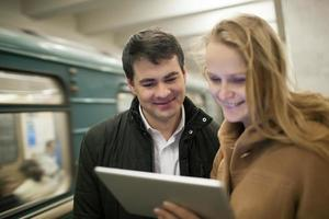 Couple using a tablet in subway station