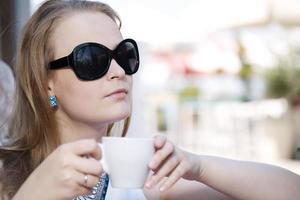 mujer joven tomando café con gafas de sol foto