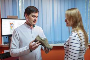 Woman being consulted by a foot doctor photo