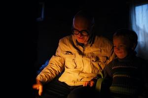 Grandfather and grandson near a fire.