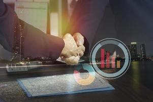 Double exposure of businessmen shaking hands with graphs overlay photo