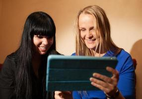 Two young women using a tablet