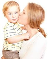 Mother kissing son on a white background