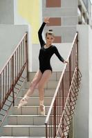 Young ballerina posing on stairs photo