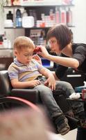 Boy getting a haircut in a salon photo