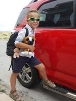 Boy with a stuffed dog with a vehicle