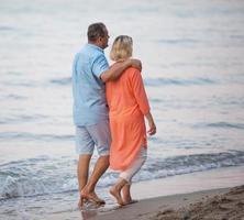 Pareja madura disfrutando de un paseo descalzo en la playa.