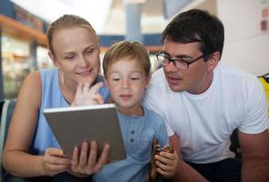 padres e hijo con tableta en el aeropuerto.