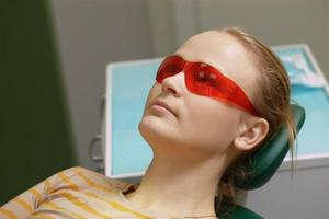 Woman in red safety glasses in a dental office