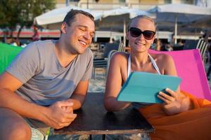 hombre y mujer en una playa con una tableta foto