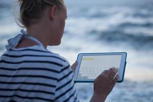 Woman typing on tablet outside
