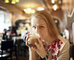 Woman drinking a latte in a coffee shop photo