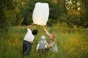Family lighting a paper lantern photo