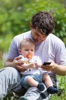 Father holding child while on phone