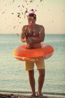 Man throwing confetti on a beach