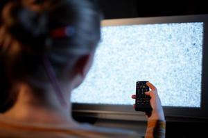 mujer con un control remoto frente a un televisor foto