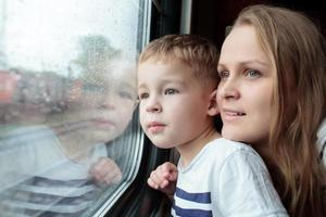 Mother and son looking out a train window photo