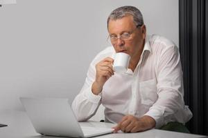 empresario tomando café mientras trabajaba en la oficina foto