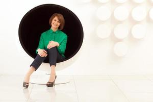 Woman sitting on a spherical chair