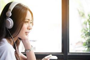 Mujer joven escuchando música en auriculares con fondo de ventana