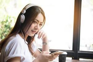 mujer joven escuchando música en auriculares con fondo de ventana.