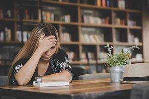 Mujer de negocios sintiéndose estresada mientras está sentado en el café foto