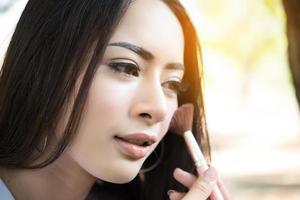mujer joven, poniendo, maquillaje, cepillo, en, ella, mejilla foto