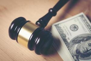Concept of legal court gavel on assorted cash, close-up