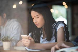 Young women using and looking at smartphone at window cafe photo