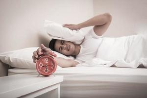 Man turns off the alarm clock in the morning