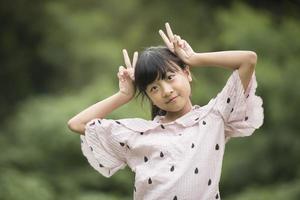 Retrato de una niña asiática jugando con la cámara foto