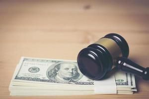 Concept of legal court gavel on assorted cash, close-up photo
