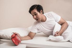 Man turns off alarm clock in a hurry