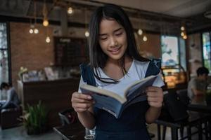mujer joven, libro de lectura, sentado, adentro, en, urbano, café