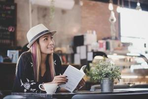 Happy business woman reading book while relaxing at cafe photo