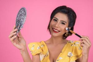 Fashionable woman with makeup and mirror photo