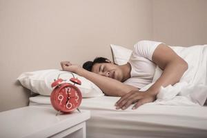 Man sleeps in bed with red alarm clock
