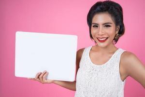 Retrato de una mujer de moda mostrando una pancarta blanca foto
