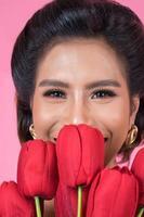 Retrato de una bella mujer con ramo de flores de tulipán rojo