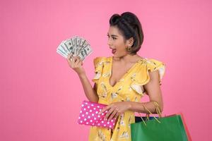 Mujer de moda joven sosteniendo una billetera con efectivo y bolsas de compras foto